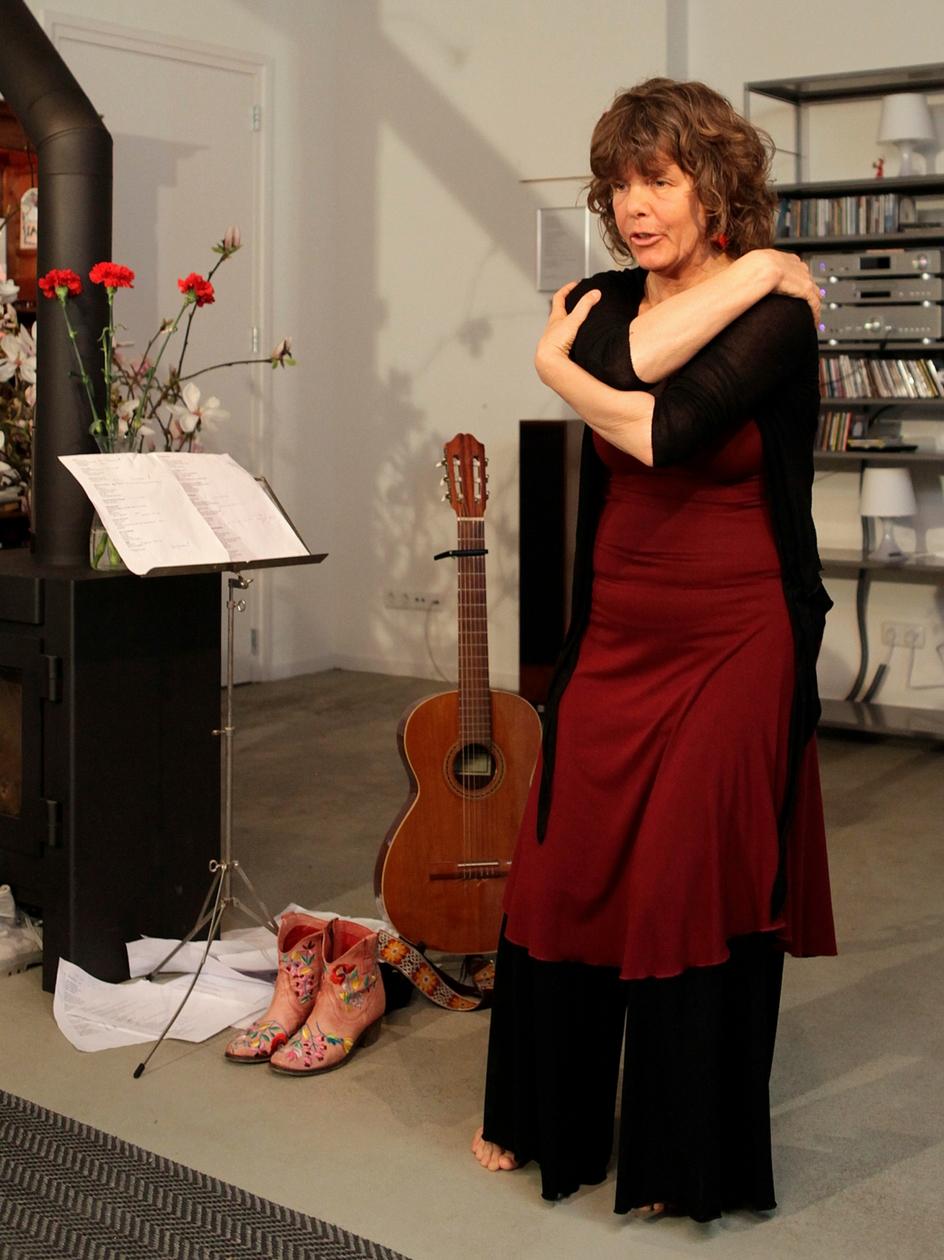 Dineke de Velde Harsenhorst draagt een gedicht voor tijdens een huiskamerconcert.
