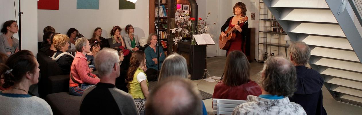 Tijdens een huiskamerconcert met veel publiek. Intens zingend en aandachtig publiek.